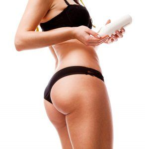 A woman applying anti cellulite cream