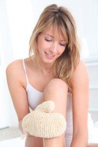 Beautiful woman using rubbing glove