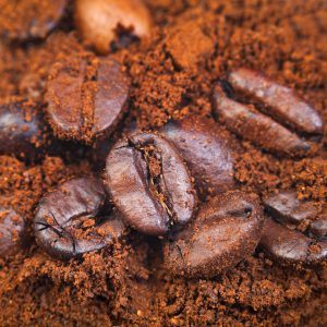 roasted coffee beans in ground coffee close up