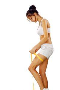 Young happy woman measures her leg on white background with path