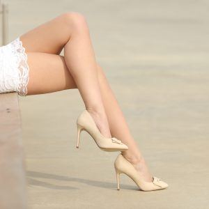 Beauty woman waxed legs sitting on a bench in the street. Laser cellulite removal concept