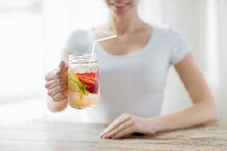 close up of happy woman holding glass with fruit water at home