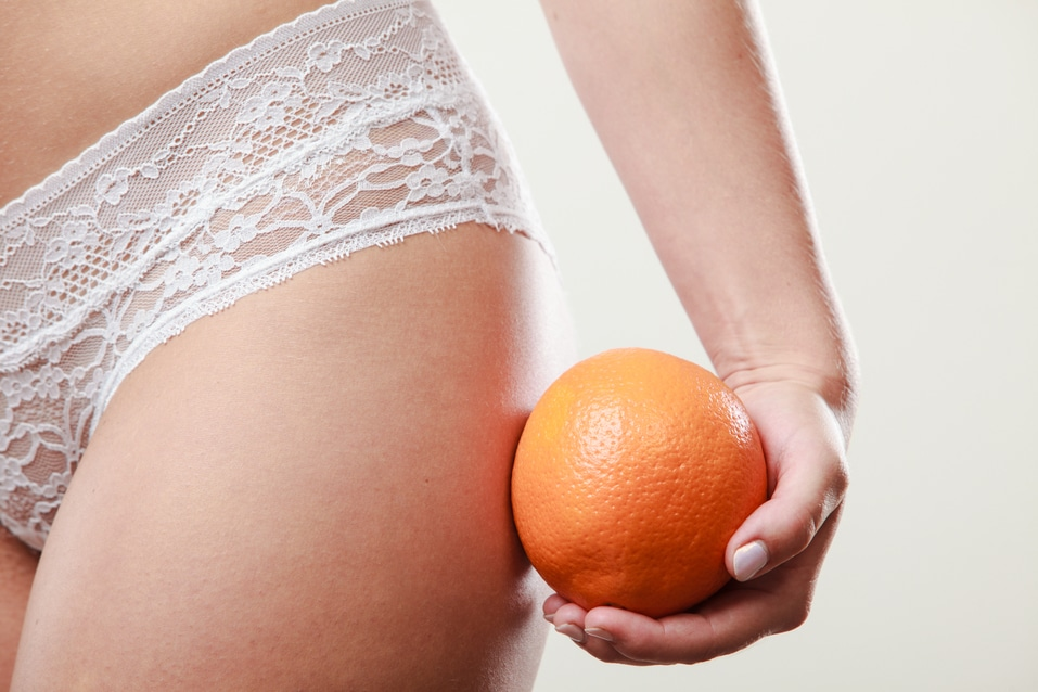 Absence of cellulite. Part body of slim fit girl holding orange next to the bottom buttocks. Woman wearing white lacy lingerie. Diet aspects.
