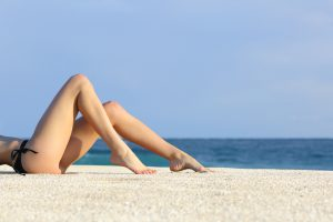Profile of a beautiful woman legs resting on the beach sunbathing with the horizon in the background