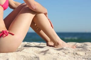 Sunbather woman legs sitting on the sand of the beach resting with the sea in the background