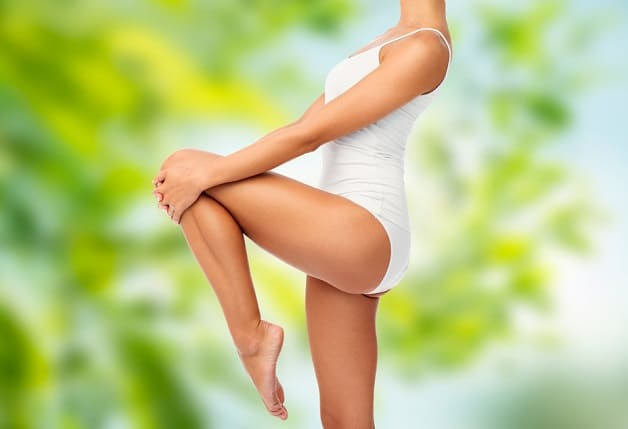 close up of beautiful young woman in white underwear over green natural background