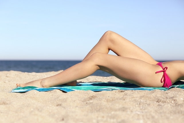 Beauty perfect woman waxing legs sunbathing on the sand of the beach with horizon in the background