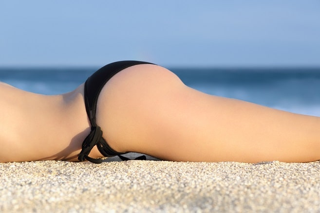 Profile of a butt of a woman with a bikini sunbathing resting on the beach with the horizon in the background