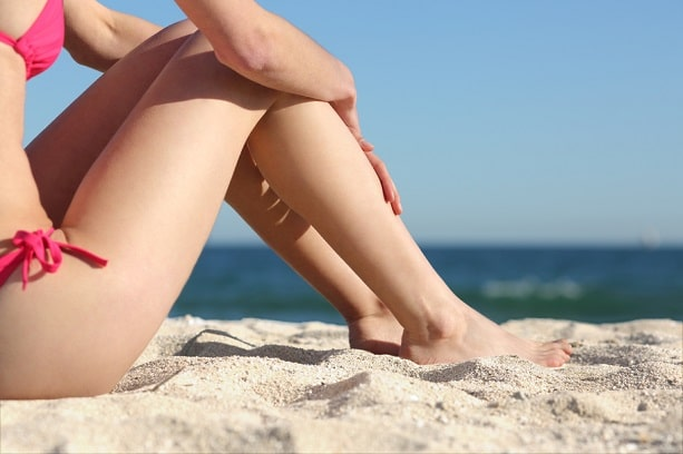 Sunbather woman legs without cellulite sitting on the sand of the beach resting with the sea in the background