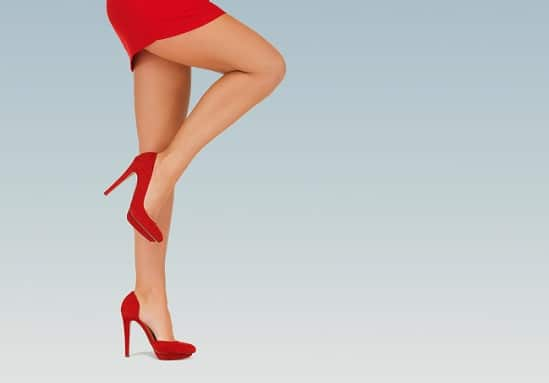 close up of woman legs in red high heeled shoes over blue background