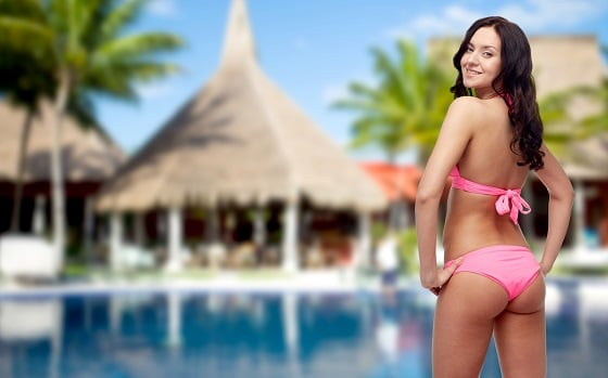 Happy sexy young woman without cellulite in pink bikini swimsuit looking back over hotel resort with swimming pool, bungalow and palm trees background