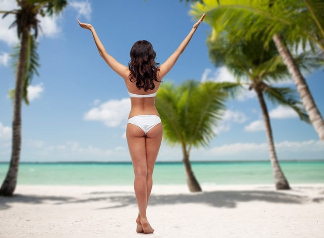 young woman without cellulite, posing in white bikini swimsuit with raised hands from back over tropical beach with palm trees background
