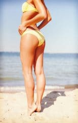 summer holidays - girl without cellulite posing in bikini on the beach