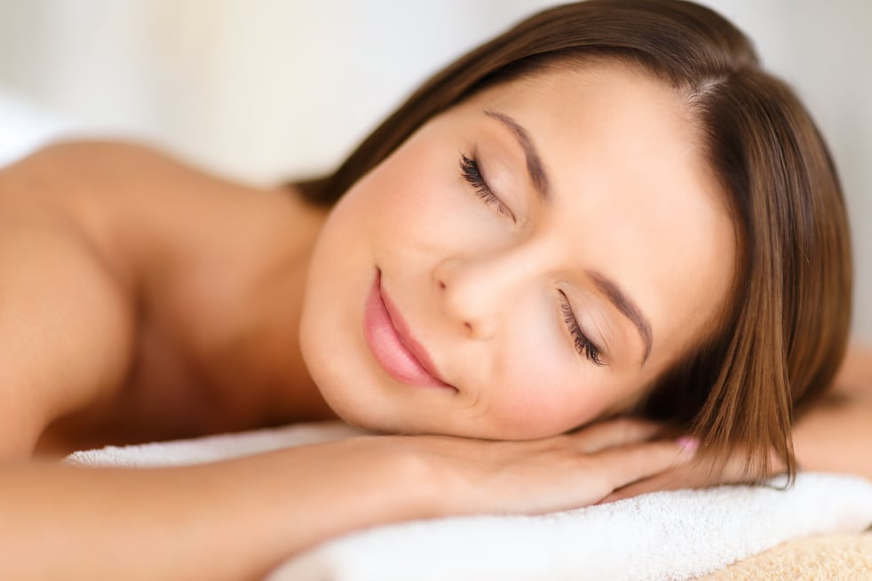 beautiful woman with closed eyes in spa salon lying on the massage desk