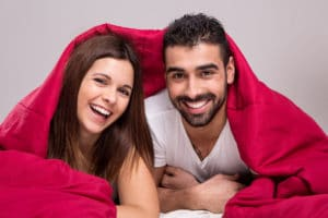Young love couple relaxing together in bed