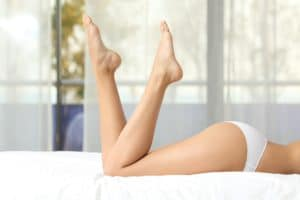 Profile of a perfect woman waxed legs lying on a bed at home