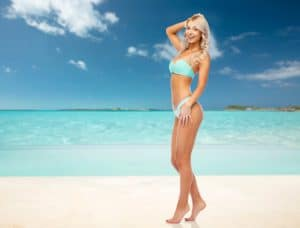 happy smiling young woman in bikini swimsuit on exotic tropical beach