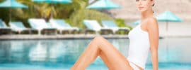 beautiful young woman in cotton underwear showing smooth skin of her legs over exotic hotel resort beach with swimming pool and sunbeds