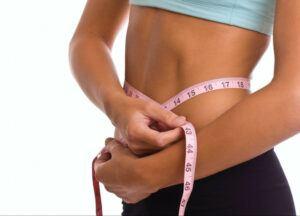 a slim woman measuring her waist
